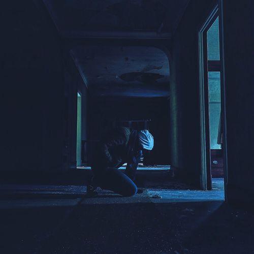 Man Kneeling In Abandoned House