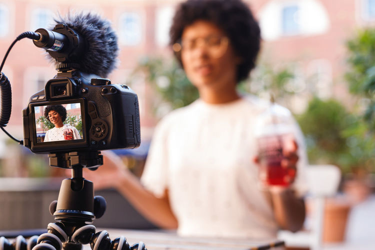 Woman Blogger Vlogger Photography Streaming Vacation Shooting Looking Social Media Girl Outdoors Online  Drink Lifestyle Young African American Camera Holding Females One Person Real People Technology Selective Focus