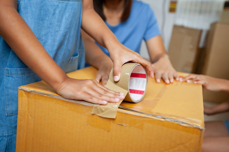 Midsection of girl packing cardboard box at home