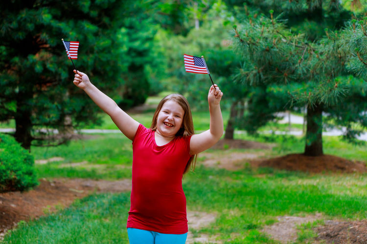 Cute overweight girl with small american flags standing at public park