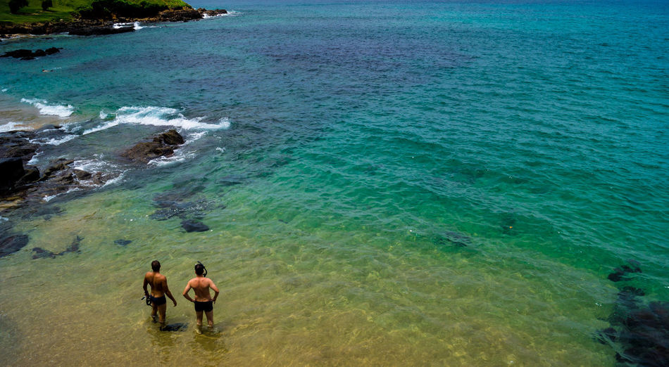 High angle view of men standing in sea