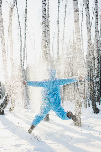 Rear View Of Mid Adult Man Jumping On Snow Covered Field In Forest