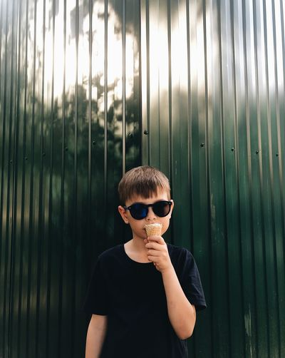 Portrait of boy eating ice cream cone while standing against corrugated iron