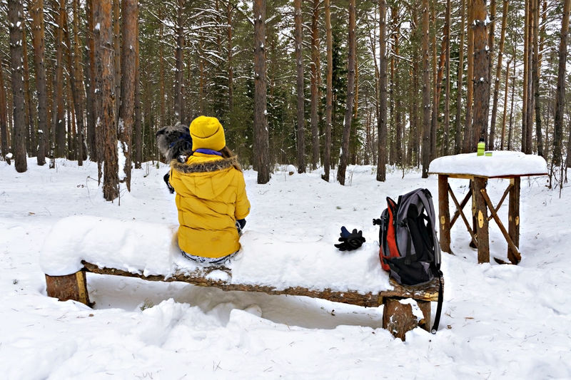 Young woman in yellow  sitting on snow covered bench in winter forest and holding fluffy dog, hiking