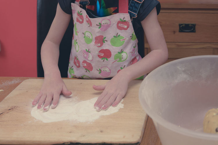 Midsection of girl kneading flour at home