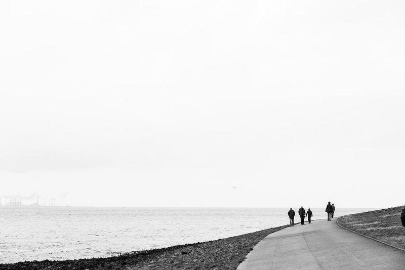 People walking on road by sea against clear sky