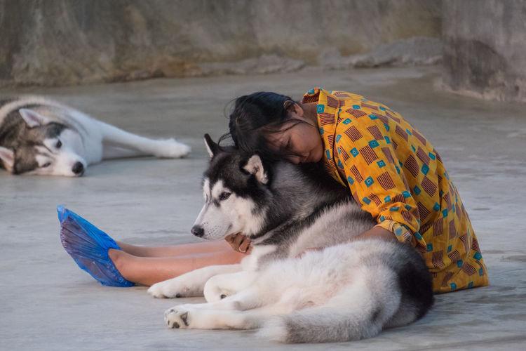 Woman embracing dog on footpath