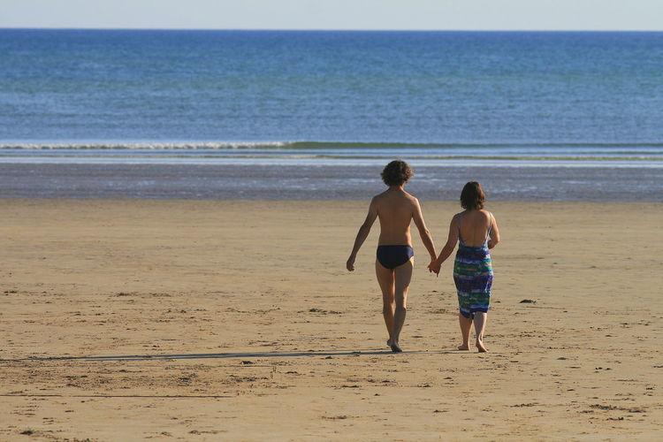 Rear view of siblings walking on beach
