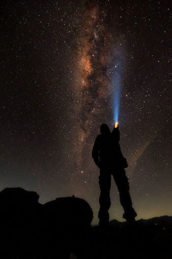 Rear view of silhouette man holding flashlight against star field