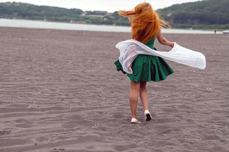 Full length rear view of woman dancing at sandy beach