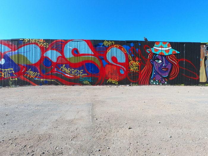 Graffiti on wall against clear blue sky