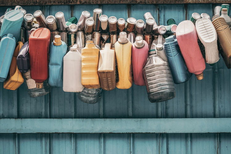 Plastic containers hanging against blue wall