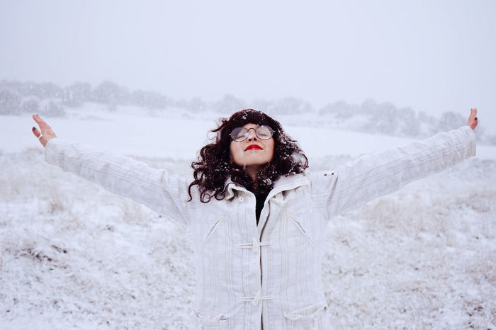 Young woman with arms outstretched standing on field during snowfall