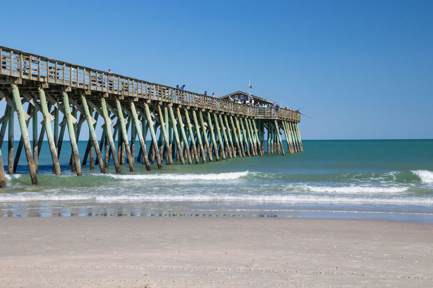 Pier at Myrtle Beach State Park Aquatic Sport Architectural Column Architecture Beach Beauty In Nature Built Structure Clear Sky Day Horizon Horizon Over Water Land Motion Nature No People Outdoors Pier Sand Scenics - Nature Sea Sky Water Wave