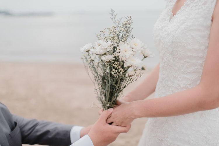 Midsection Of Groom Holding Hands Of Bride With Bouquet At Beach