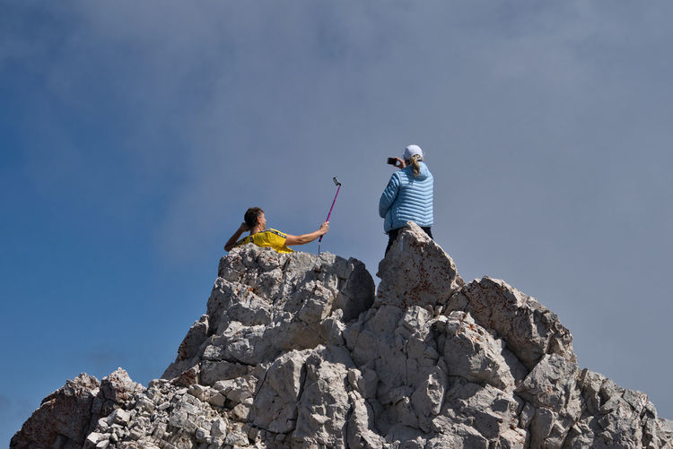 Low angle view of men on rock against sky