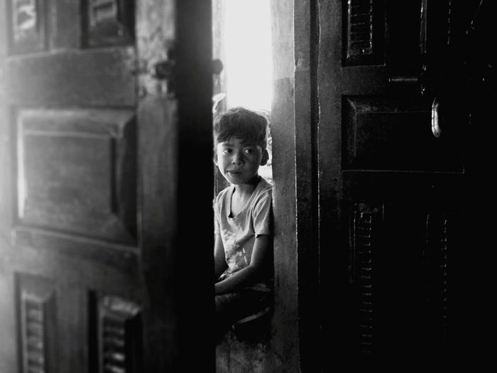 EyeEm Selects Blackandwhite Rural Village Child Childhood Portrait Boys Warm Clothing Standing Curly Hair Looking At Camera Window Domestic Room