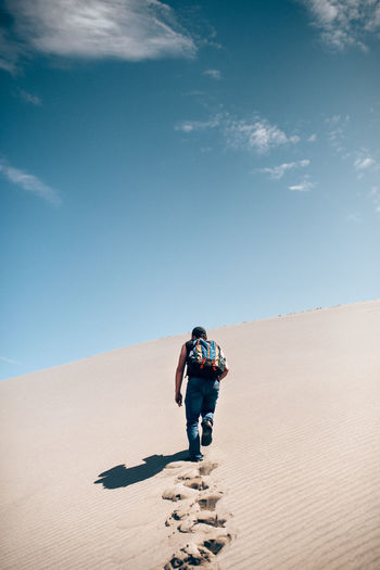 Rear view of man walking on sand dune in desert against sky