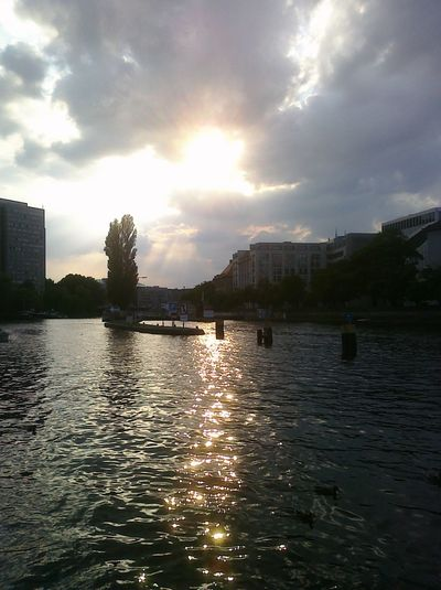 Sunset over river with city in background