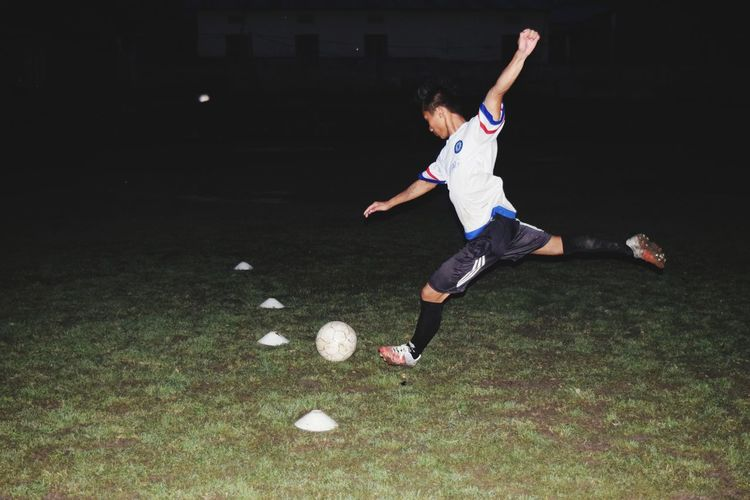 Full Length Of Man Playing Soccer On Field At Night
