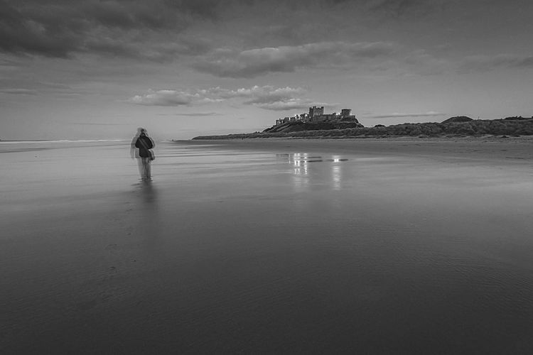 Sandy Dusk People And Places Tranquil Scene Beach Scenics Tranquility Reflection Solitude Beach Photography Beach Reflections EyeEm Masterclass Idyllic Landscape Bamburgh Northumberland Lone Walker BW Collection Beach Walk Long Exposure Shot Beach And Sky Coastline Beauty In Nature Atmospheric Mood Monochrome Photography Finding New Frontiers