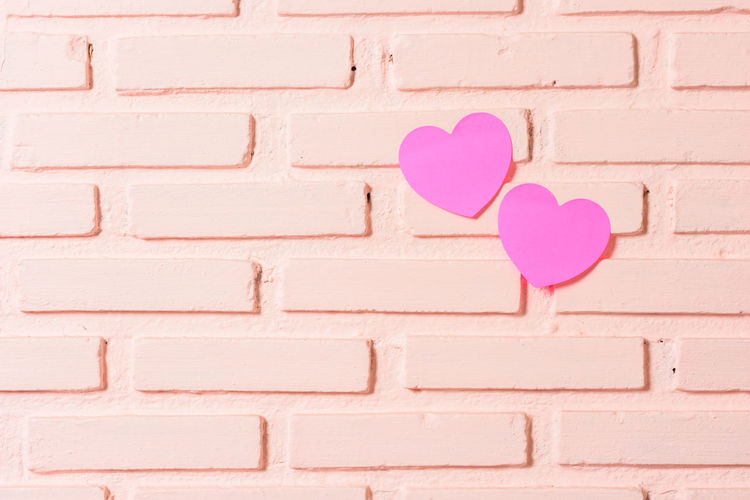 Close-up of heart shape on pink wall