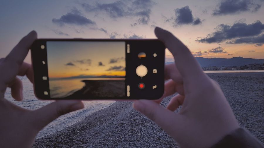 Midsection of person using mobile phone against sky during sunset