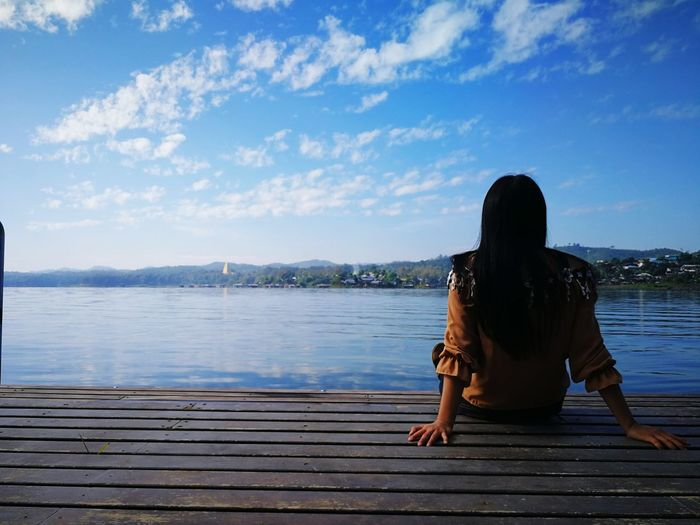Rear view of mid adult woman sitting by lake against sky