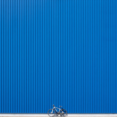 Bicycle parked against blue corrugated iron