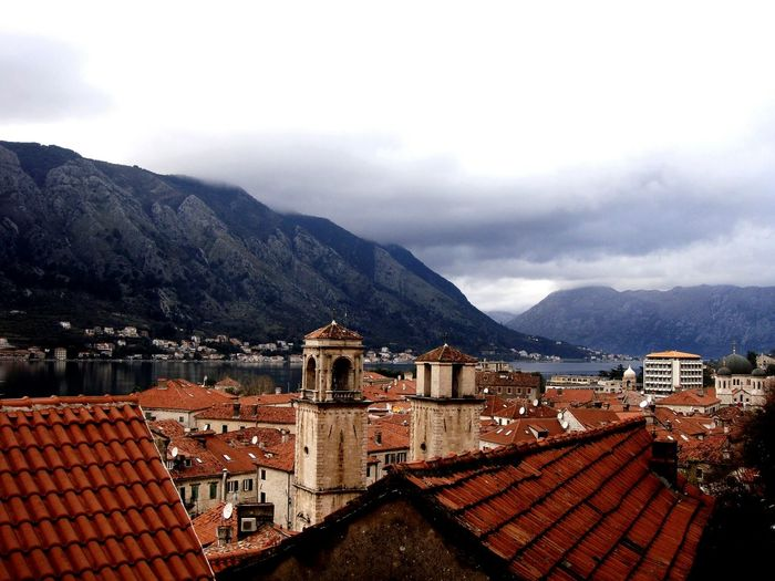 Kotor by sea and mountains against sky