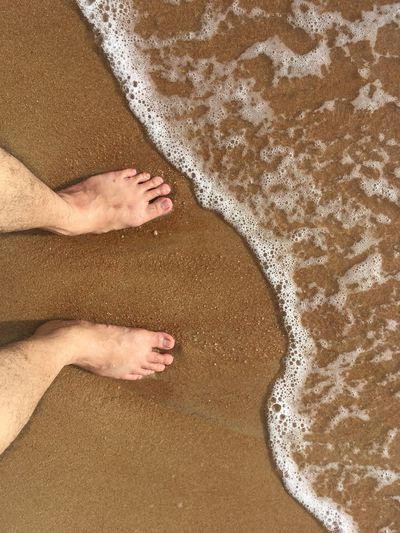 Low section of person on sand at beach