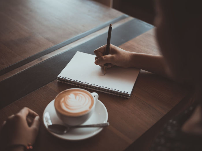 Cropped Hands Of Woman Writing On Book With Coffee On Table