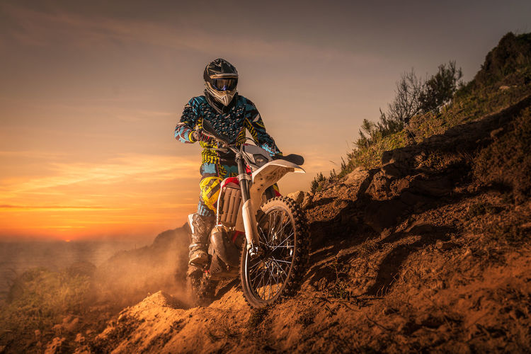Man riding motorcycle on mountain against sky during sunset