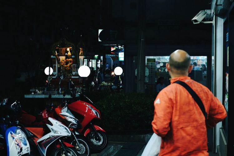 Rear view of man by shop at night