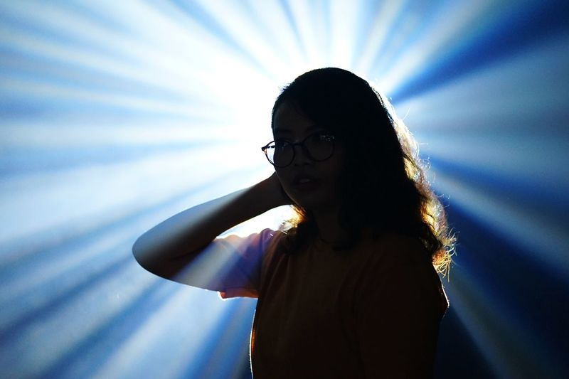 Young woman standing against light beams