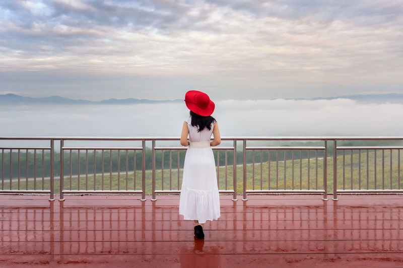 Beautiful woman over cloud, Her wear white dress and red hat standing View point on Tung Bua Tong Mexican sunflower field in Mae Moh Coal Mine, Lampang Province, Thailand. Railing One Person Standing Sky Real People Full Length Cloud - Sky Lifestyles Casual Clothing Women Adult Nature Leisure Activity Rear View Clothing Day Fashion Hat Young Adult Outdoors Hairstyle Looking At View