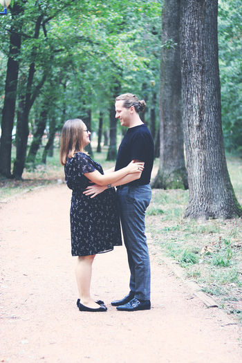 Side view of couple standing on road in forest