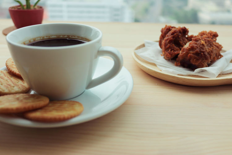 Close-Up Of Coffee And Biscuits By Fried Chicken On Table