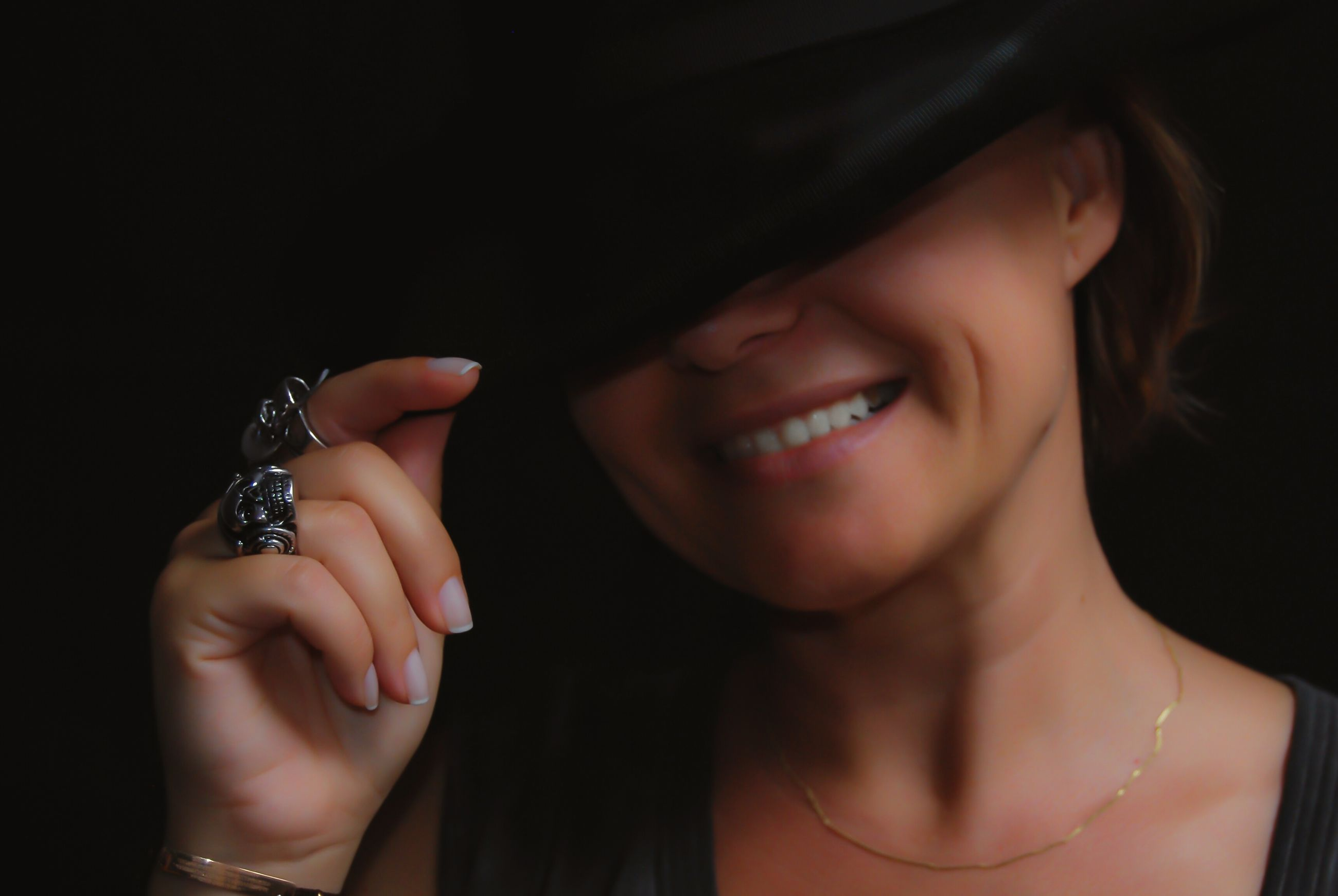 CLOSE-UP PORTRAIT OF A SMILING YOUNG WOMAN HOLDING BLACK BACKGROUND