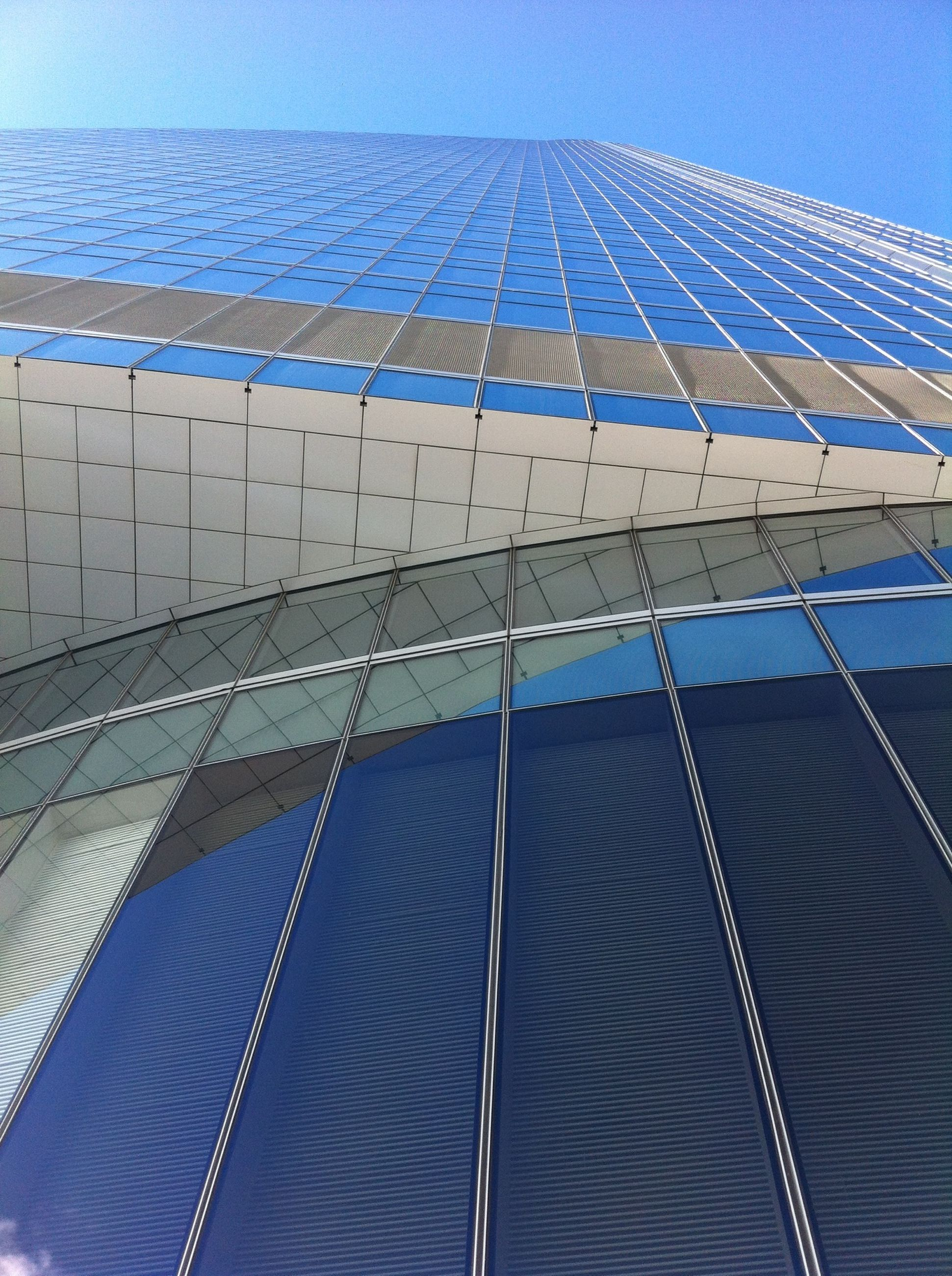 low angle view, blue, built structure, pattern, architecture, modern, building exterior, clear sky, sky, day, outdoors, sunlight, office building, skyscraper, design, city, diminishing perspective, repetition, tall - high, part of
