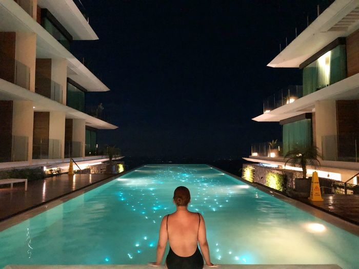 Woman swimming in pool at night