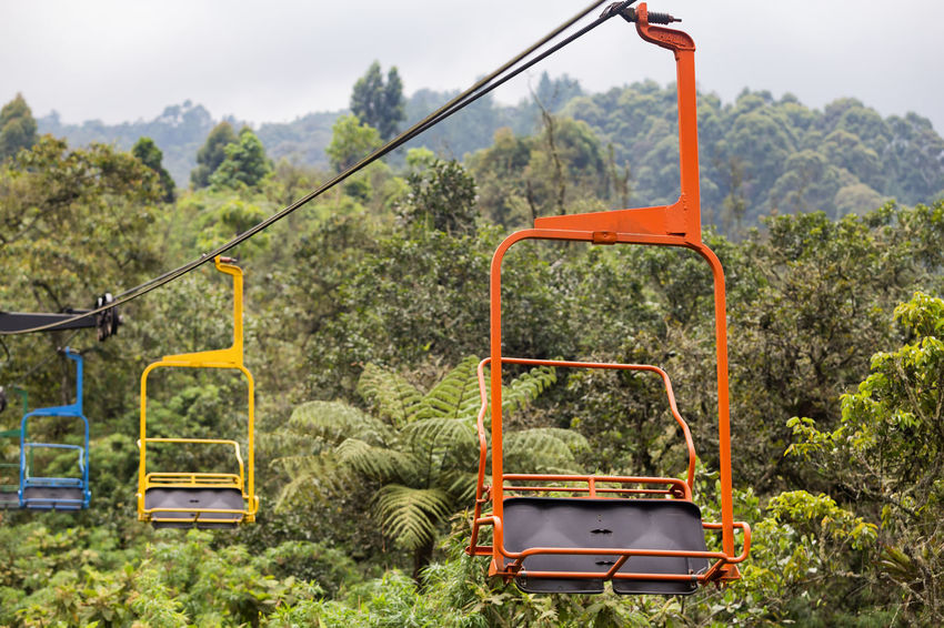 Orange, yellow, and blue chairs on the ski lift at the Recinto del Pensamiento nature reserve near Manizales, Colombia. Chair Cloud Colombia Electric Green Latin Manizales Recinto Ski Lift South America Andean Cloud Forest Coffee Triangle Colombian  Colorful Day Fog Forest Lift Mist Nature Outdoors Park Pensamiento