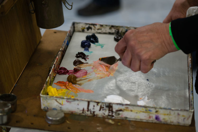 ArtWork Artist Palette Knife Art And Craft Art And Craft Equipment Body Part Craft Creativity Finger Hand Holding Human Hand Indoors  Messy Multi Colored Occupation One Person Paint Painting Palette Palette Colors Real People Skill  Unrecognizable Person