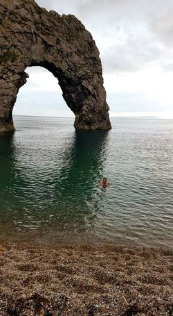 Swimming at Durdle Door, Dorset Durdle Door Dorset Sea Ocean Beachphotography Area Of Outstanding Natural Beauty Water Sea Beach Natural Arch Sand Rock - Object Arch Rock Formation Sky Horizon Over Water Stack Rock Geology Rocky Coastline Natural Landmark Pebble Beach Eroded Physical Geography Calm Cliff Pebble Seascape Rugged Summer Exploratorium Focus On The Story Modern Hospitality The Architect - 2018 EyeEm Awards The Great Outdoors - 2018 EyeEm Awards