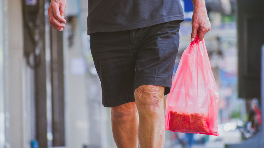 Midsection of man holding plastic bag while walking in city