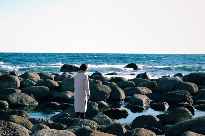 Rear view of woman standing at beach on sunny day
