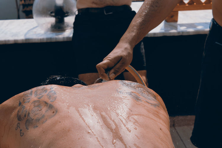 Midsection of man cleaning friend with water