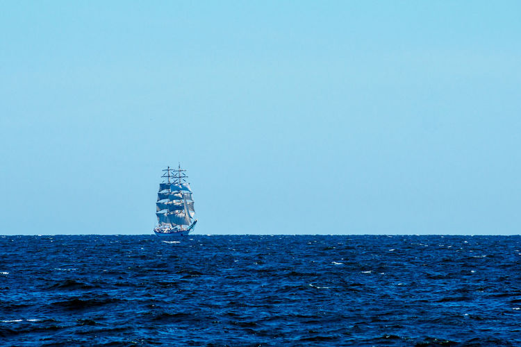 Sailboat in sea against clear blue sky