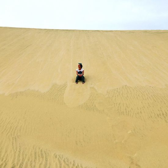 Low angle view of man sitting on sand dune against clear sky