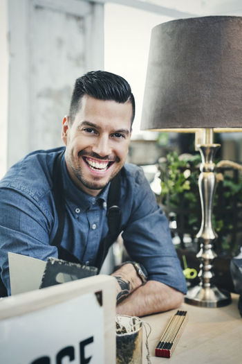 Portrait of smiling man sitting at table